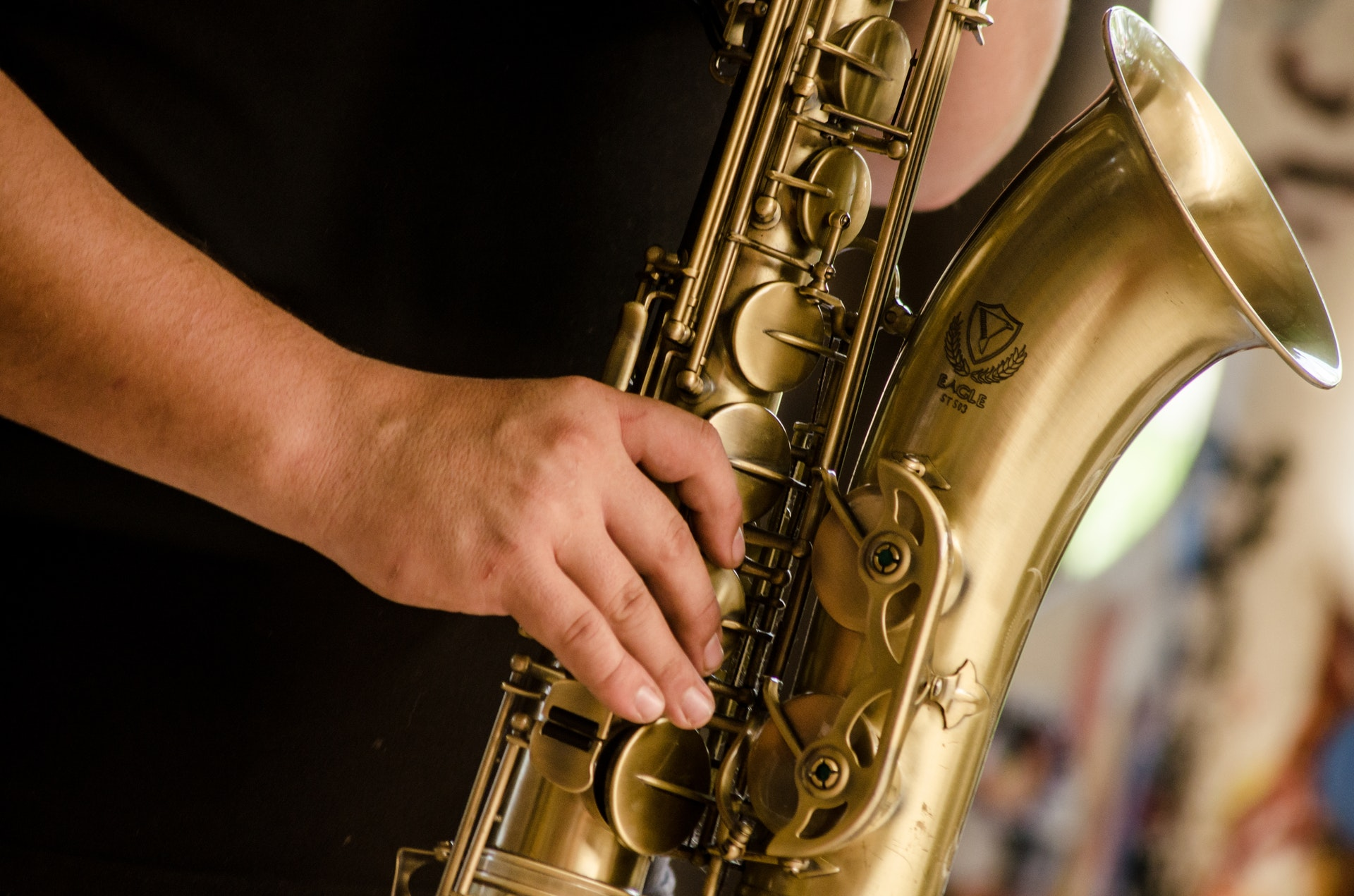 Person in black shirt playing brass colored saxophone 1049690
